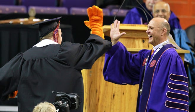 Christopher Glenn Alston, wearing tiger paw gloves, gives Jim Clements, 15th president of Clemson University, a high-five during the morning graduation in Littlejohn Coliseum. Alston was one of the students who played the Clemson Tiger during 2014.