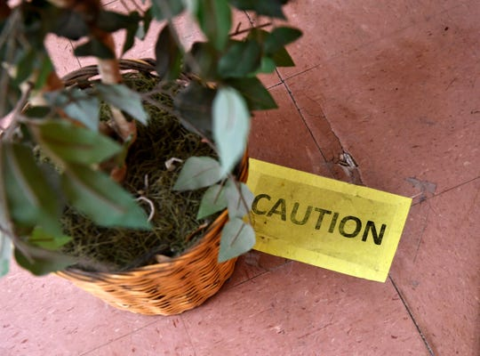 A sign and a potted artificial plant keep students and staff away from a hole in the floor at ATEMS.