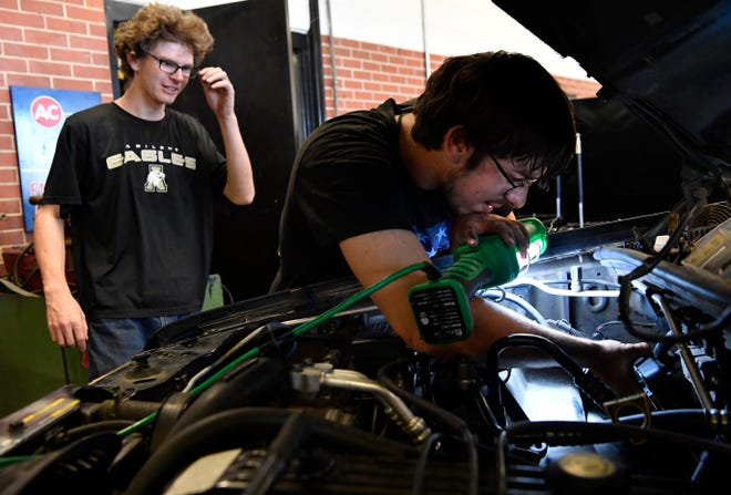 Seniors Billy Harwood (left) and David Evinger install a computer module in a pickup Tuesday in Abilene High School's auto shop.