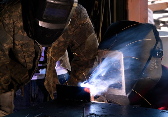 Jacob Arredondo (left) watches Zack Vigil weld a bead on piece of steel Tuesday at Cooper High School's welding shop.