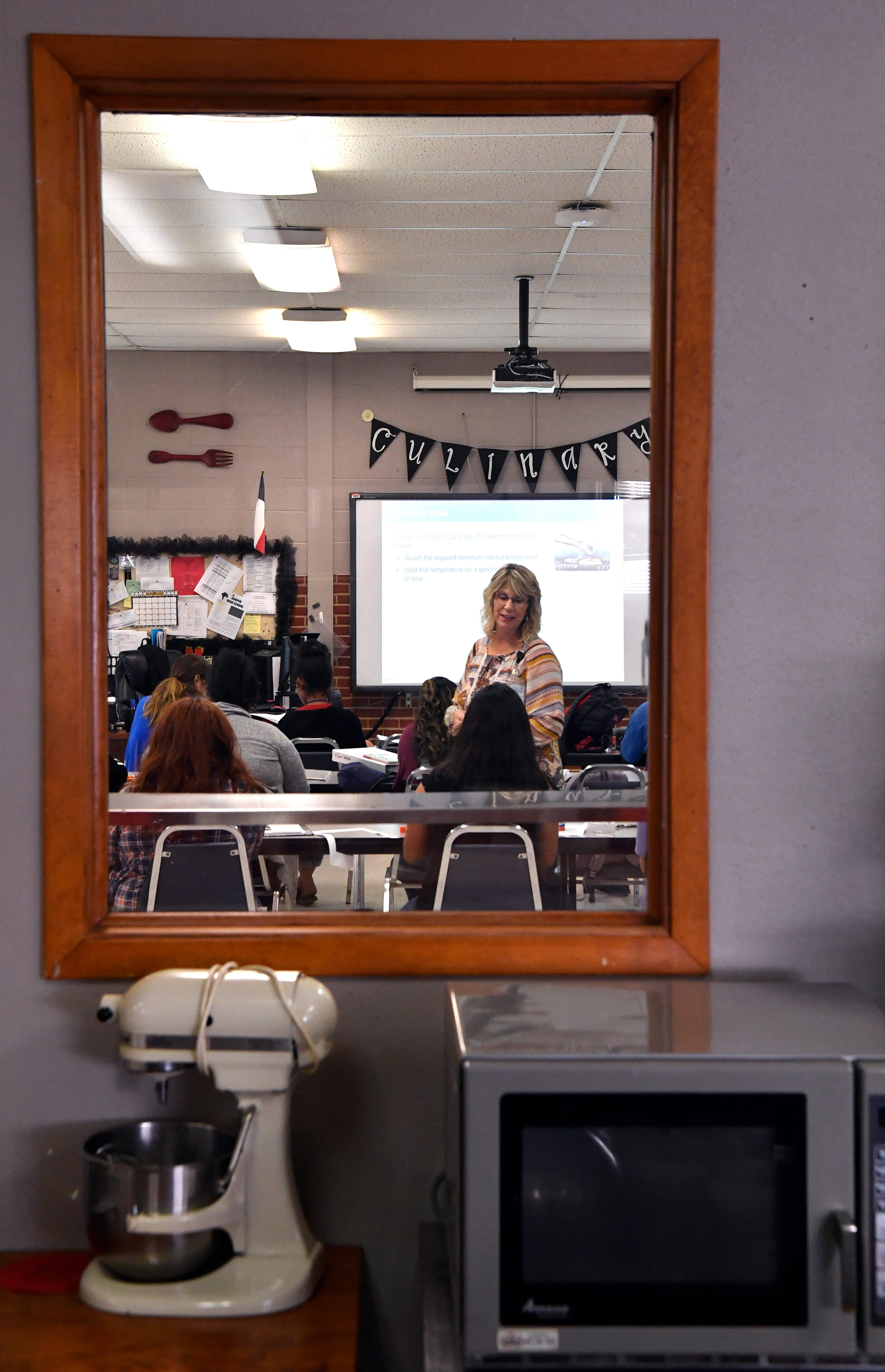 Tina Watson is framed in the window separating her culinary arts classroom from the kitchen laboratory during class Tuesday.