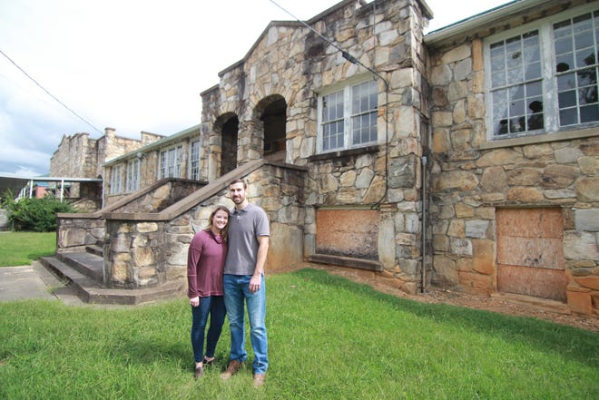 Alex and Audrey Worley stand outside the old Mars Hill High School Building. Renovations are in the planning stage to transform the 1930s building into a 16-unit rental apartment complex.