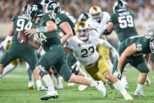 Michigan State Spartans quarterback Brian Lewerke (14) is sacked by Notre Dame Fighting Irish linebacker Drue Tranquill (23) in the first quarter at Spartan Stadium.