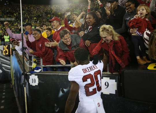 Fans celebrate with Bobby Okereke at Autzen Stadium after Stanford's 38-31 overtime victory against Oregon in an NCAA college football game Saturday. Such evening Pac-12 games are likely to remain a fixture of ESPN and Fox broadcasting schedules.