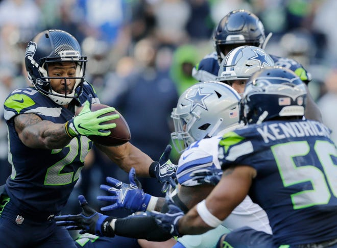 Seahawks free safety Earl Thomas, left, intercepts a pass during Sunday's win over the Cowboys in Seattle. It was Thomas' second interception of the game.
