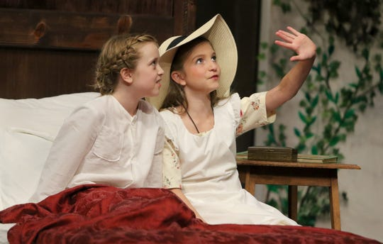 Invalid Colin (Tess Kilmer, left) listens as Mary Lennox (Kendall Runyan) describes the world outside the bedroom.
