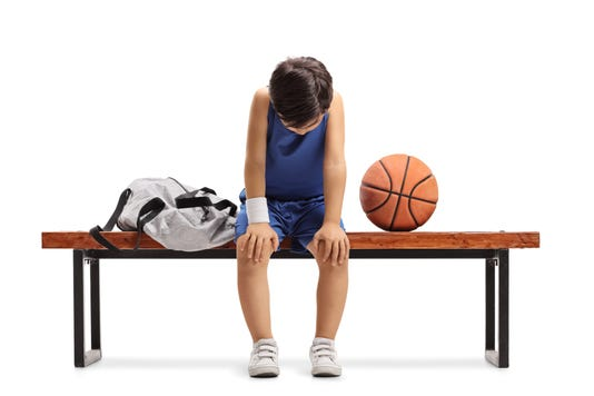 Sad Little Basketball Player Sitting On A Bench