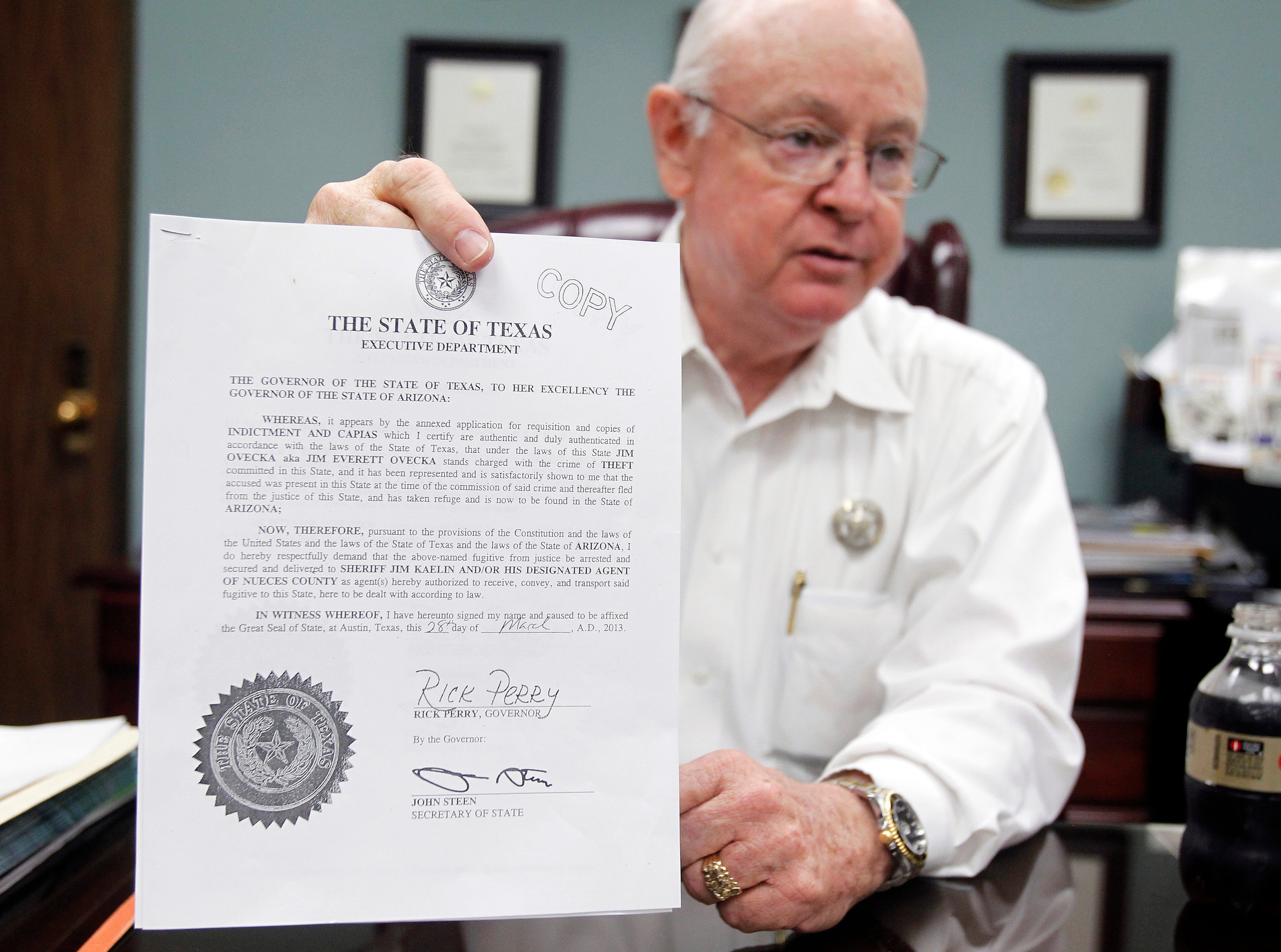 Nueces County Sheriff Jim Kaelin holds up a copy of an extradition order Thursday, Aug. 1, 2013 as he explains his department's extradition process in his office in Corpus Christi.