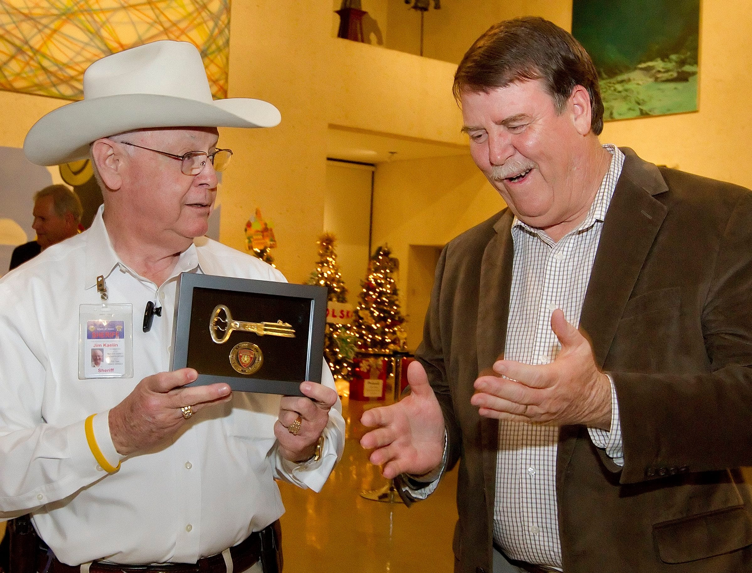 Retiring Caller-Times Publisher Darrell Coleman (right) reacts to a gift from Nueces County Sheriff Jim Kaelin (left), the Key to the Jail at the Art Museum of South Texas Wednesday, December 4, 2013.