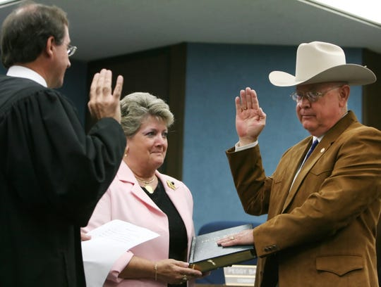 Judge Tom Greenwell (left) swears in newly elected Nueces County Sheriff  Jim Kaelin (right) as Kaelin's wife, Sharon Kaelin, holds the bible at the Nueces County Courthouse on Friday. (11/17/06)