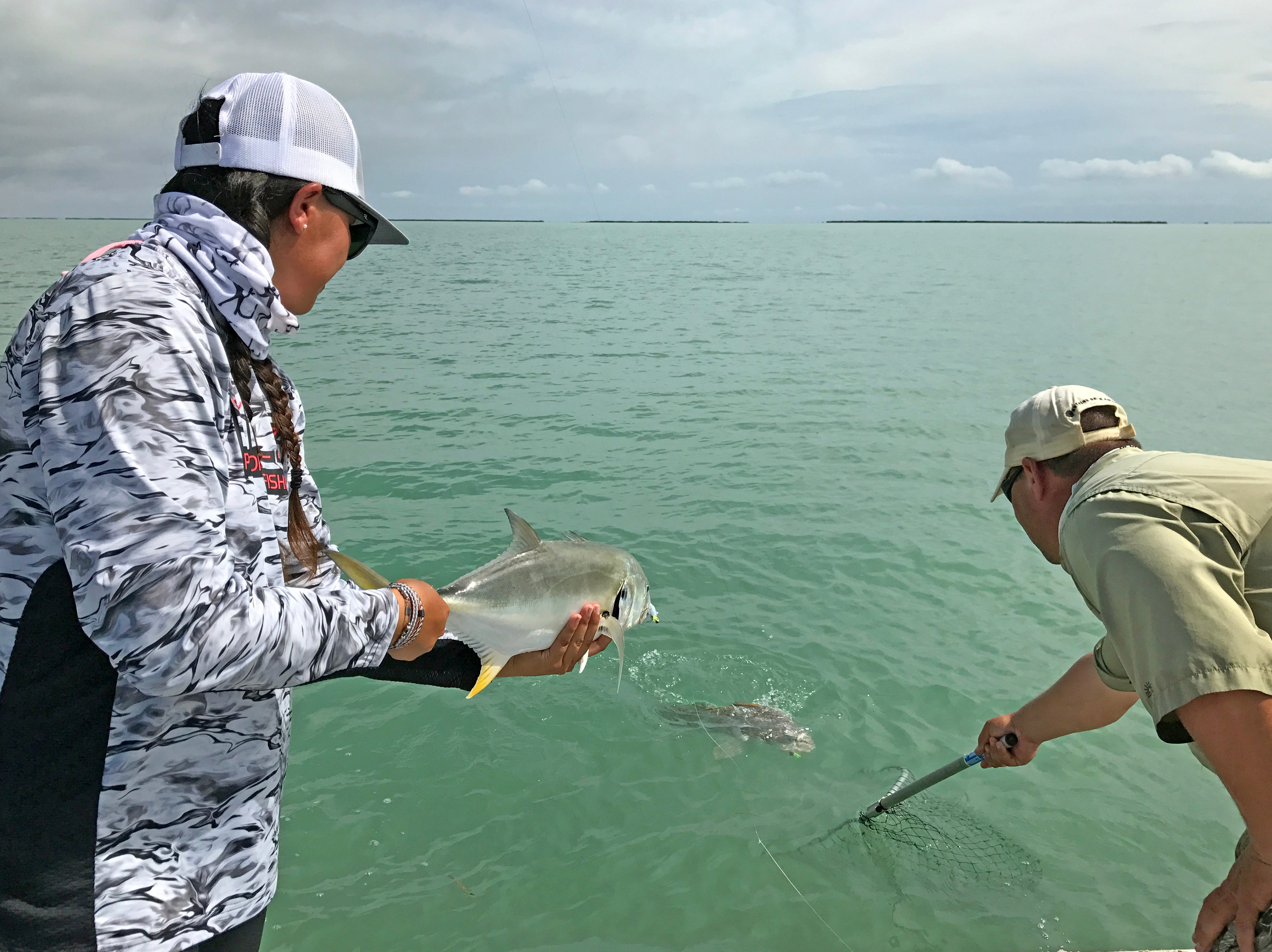 Ruby Delgado prepares to release a jackfish, while Mke Mahl nets a black drum.