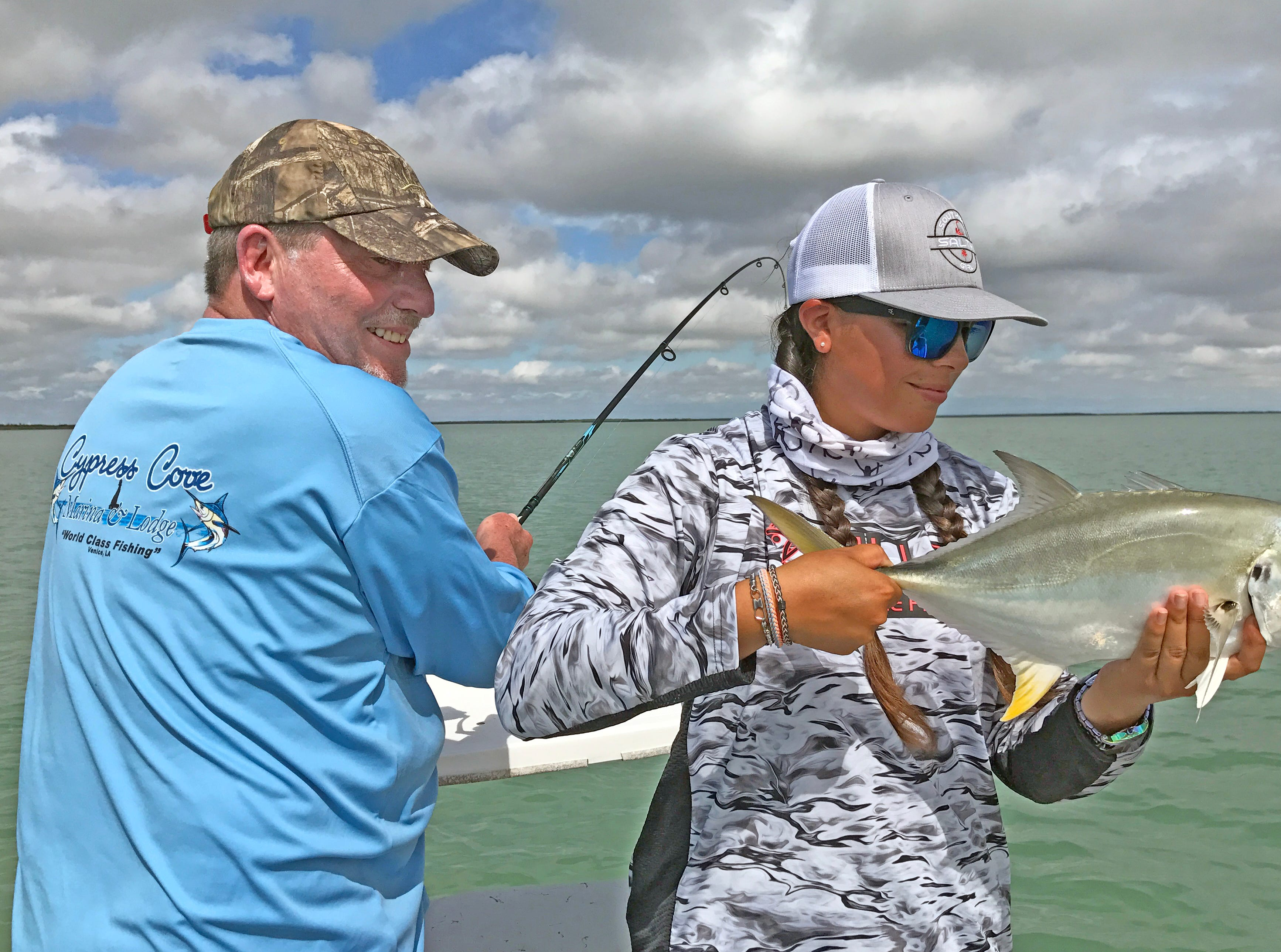 New Orleans angler Rod Felder battles a fish, while Ruby Delgado prepares to release a jack crevalle.