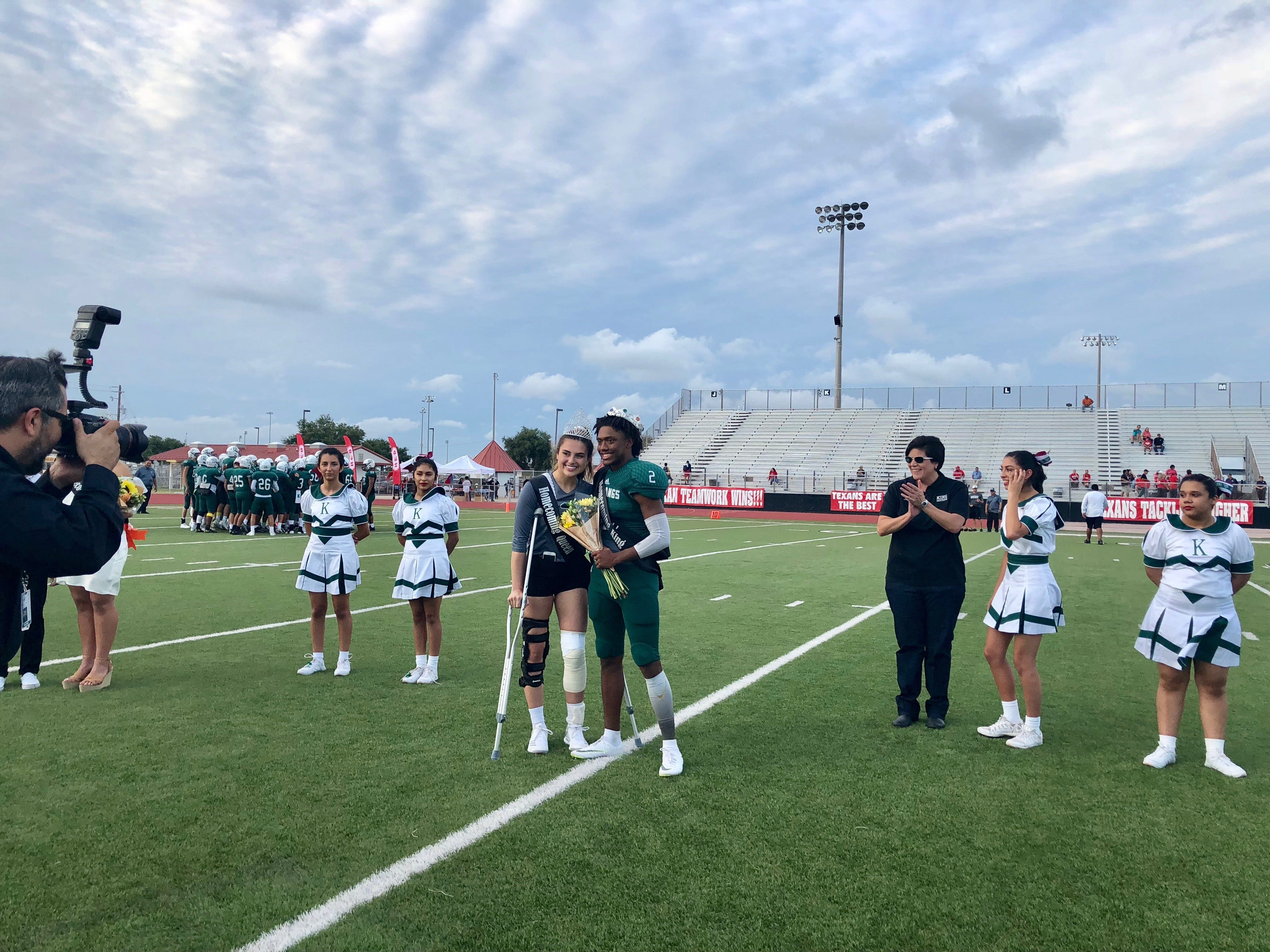 Senior homecoming queen Whitley Elizondo stands beside homecoming king Lestor Sabsook after injuring her knee at a volleyball game.