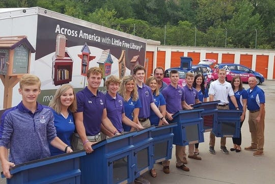 Elder High School community service program students unload 50 Little Free Libraries to be installed across the city.