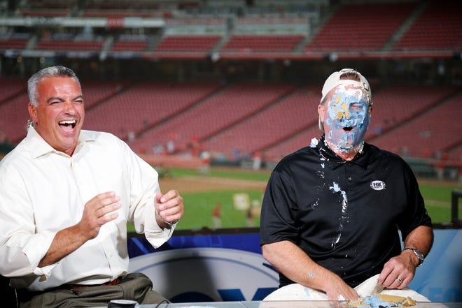 Broadcaster Jeff Piecoro smashes a University of Kentucky themed pie in the face of Jeff Brantley to settle a college football bet between the two before the MLB Interleague game between the Cincinnati Reds and the Kansas City Royals at Great American Ball Park in downtown Cincinnati on Tuesday, Sept. 25, 2018.