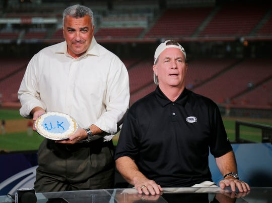 Broadcaster Jeff Piecoro shows off a University of Kentucky themed pie before smashing it in the face of Jeff Brantley to settle a college football bet between the two before the MLB Interleague game between the Cincinnati Reds and the Kansas City Royals at Great American Ball Park in downtown Cincinnati on Tuesday, Sept. 25, 2018.