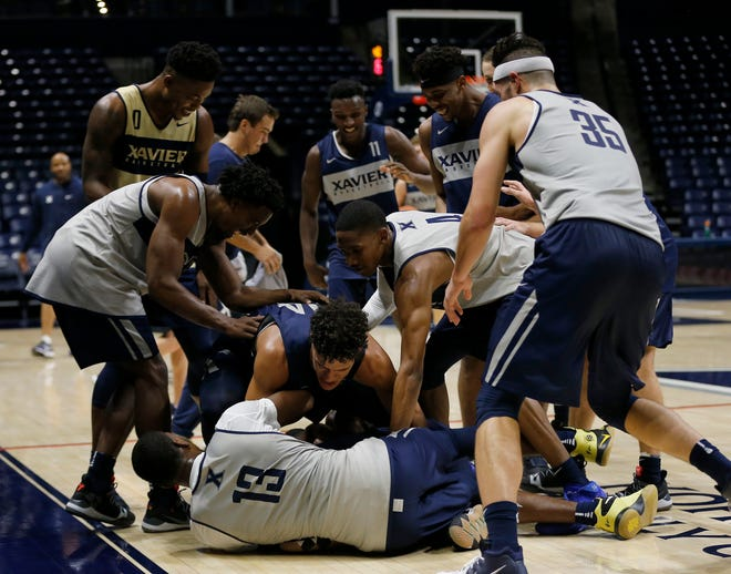 The full team chases the final loose ball drill during the first practice of the season at the Cintas Center in Cincinnati on Tuesday, Sept. 25, 2018.