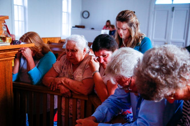 Friends and family pray for Brenda Smith during a community service at Indian Mound United Methodist on Monday.