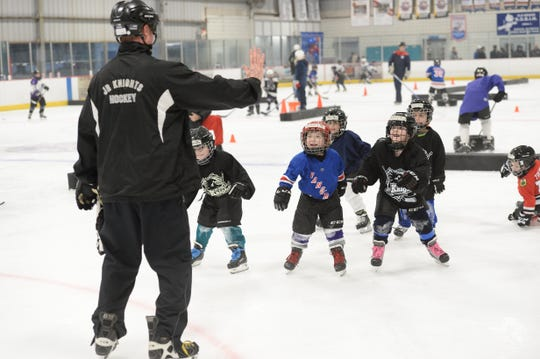 Old Bridge Jr. Knights coach and director of player development Kevin Drisscoll gives instructions to kids on the ice.