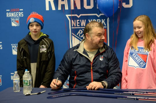 New York Rangers player alumni retired NHL player Chris Kotsopoulos signs hockey sticks for participants in the Old Bridge Jr. Knights Youth Ice Hockey program.