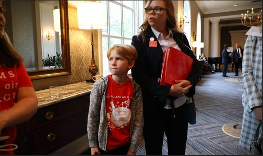 From left, Oscar Hauptman, 7 of Brighton and his mother Elizabeth Hauptman of Moms Clean Air Force gather with advocates during public hearings on the Trump administration's plans to freeze mile-per-gallon standards after 2020 at the Dearborn Inn in Dearborn, Tuesday, September 25, 2018.  Oscar has asthma and like others with health conditions and the aged, he is susceptible to air pollutants.