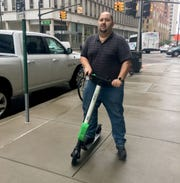 Miguel Gaytan, 35, of Temperance rides a Lime scooter in downtown Detroit on Tuesday, Sept. 25, 2018.