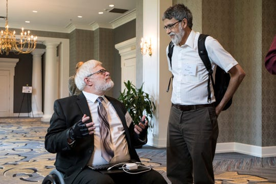 From left, James McCargar, former E.P.A. senior policy analyst speaks with Tad Wysor, engineer at Ann Arbor's National Vehicle and Fuel Emissions Laboratory during public hearings on proposed fuel economy rollbacks in Dearborn, Tuesday, September 25, 2018.