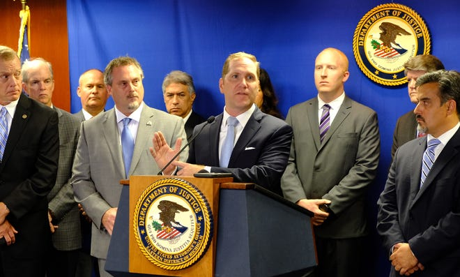 U.S. Attorney Matthew Schneider  introduces the Southeast Michigan Regional Organized Crime Drug Enforcement Task Force, Tuesday in Detroit.  Schneider points to southeast Michigan on his hand, saying there have been enough drug-related deaths to fill Tigers stadium.