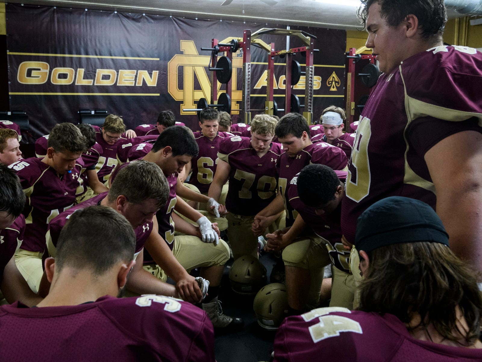 Mount Carmel's Elliot Laws (79), far right, leads a prayer before the Golden Aces take on Washington Hatchets at Riverview Stadium, known as the Snake Pit, in Mount Carmel, Ill., Friday, Sept. 21, 2018. The Golden Aces defeated the Hatchets 61-20.