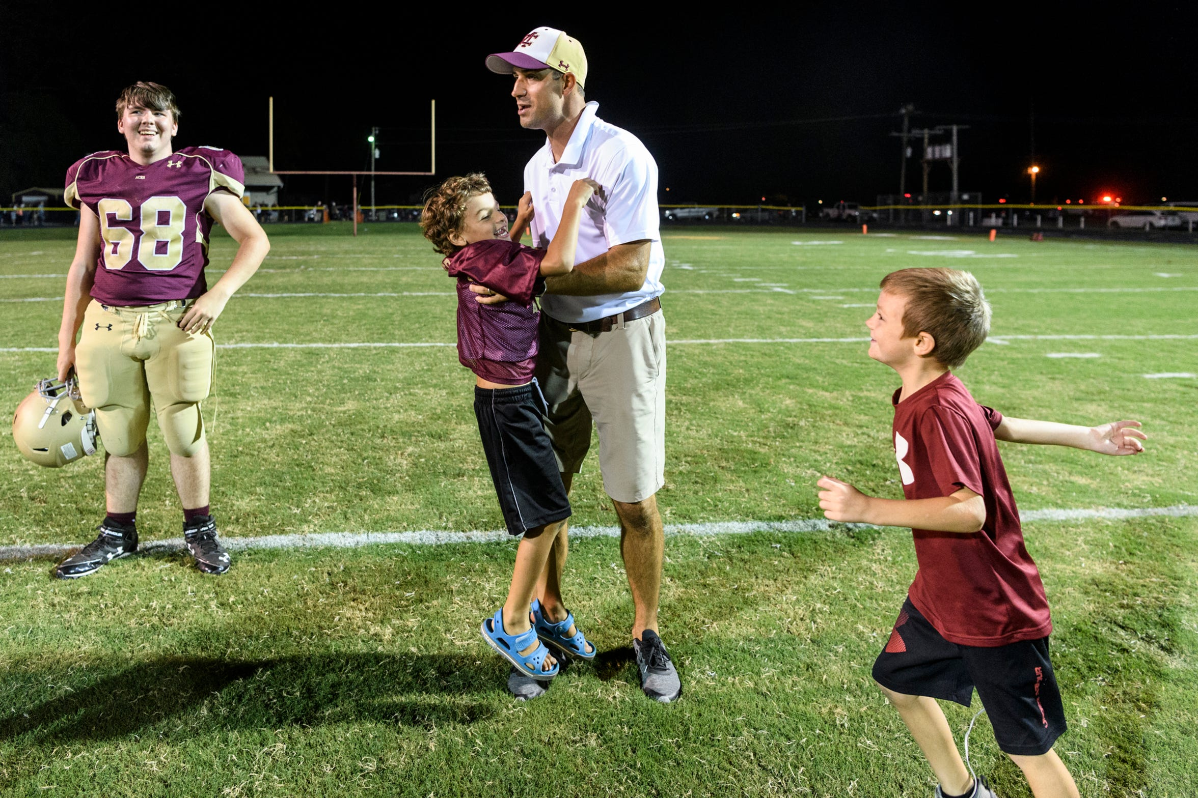 Mount Carmel Head Coach Michael Brewer, center right, is greeted by two of his children, James Brewer, center left, and Judah Brewer, right, after the Golden Aces beat the Washington Hatchets 61-20 at Riverview Stadium, known as the Snake Pit, in Mount Carmel, Ill., Friday, Sept. 21, 2018.