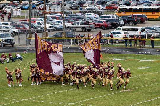 The Mount Carmel Golden Aces rush the field before the start of the Homecoming game against the Washington Hatchets at Riverview Stadium, known as the Snake Pit, in Mount Carmel, Ill., Friday, Sept. 21, 2018. The Golden Aces defeated the Hatchets 61-20.