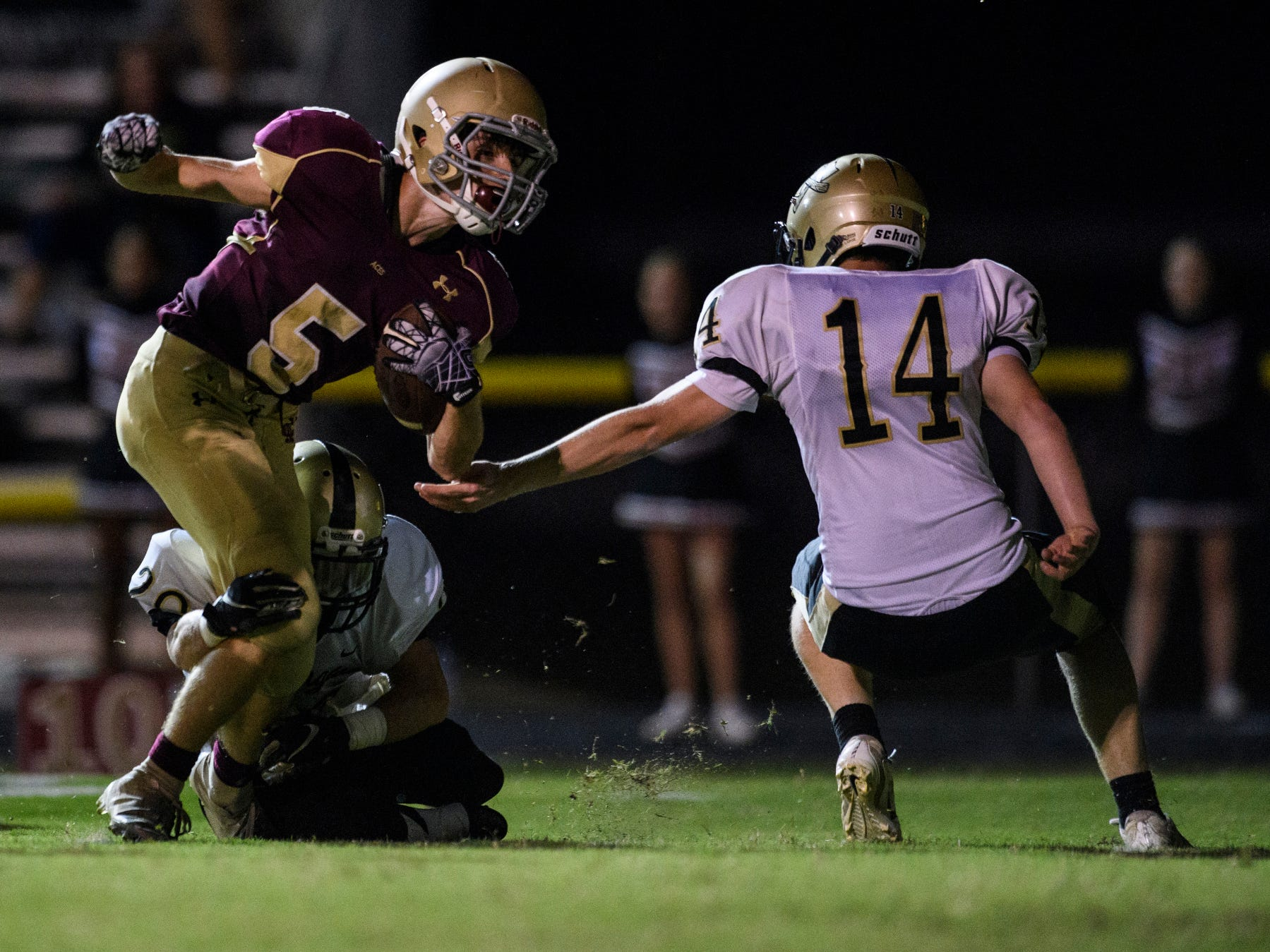 Washington's Jacob Mason (20) tackles Mount Carmel's Zeke Hadra (5) with help from Washington's Clint Ivy (14) at Riverview Stadium, known as the Snake Pit, in Mount Carmel, Ill., Friday, Sept. 21, 2018. The Golden Aces defeated the Hatchets 61-20.