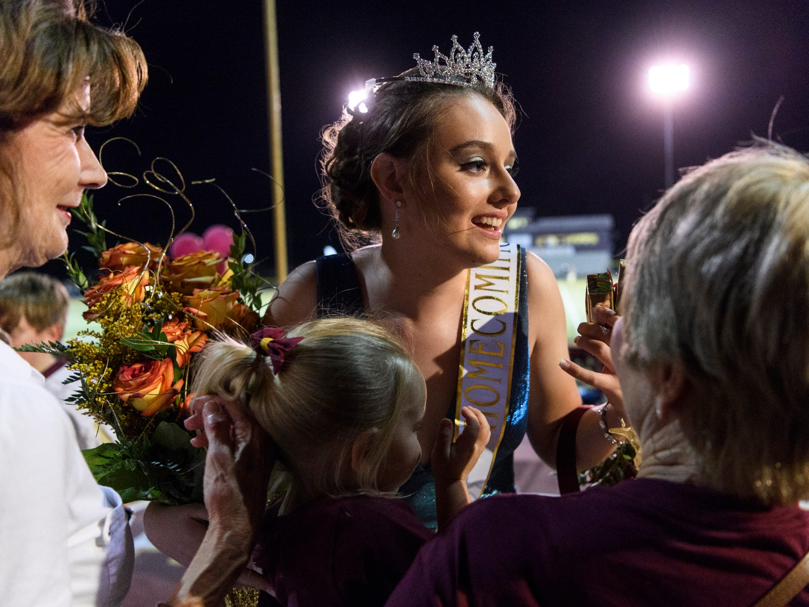 Friends and family surround newly crowned Homecoming Queen Teagan Guard, 17, during halftime of the Mount Carmel Golden Aces and Washington Hatchets game at Riverview Stadium, known as the Snake Pit, in Mount Carmel, Ill., Friday, Sept. 21, 2018. The Golden Aces defeated the Hatchets 61-20.