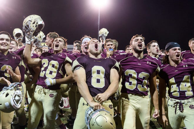 The Mount Carmel Golden Aces celebrate their 61-20 Homecoming victory over the Washington Hatchets at Riverview Stadium, known as the Snake Pit, in Mount Carmel, Ill., Friday, Sept. 21, 2018. The Golden Aces defeated the Hatchets 61-20.