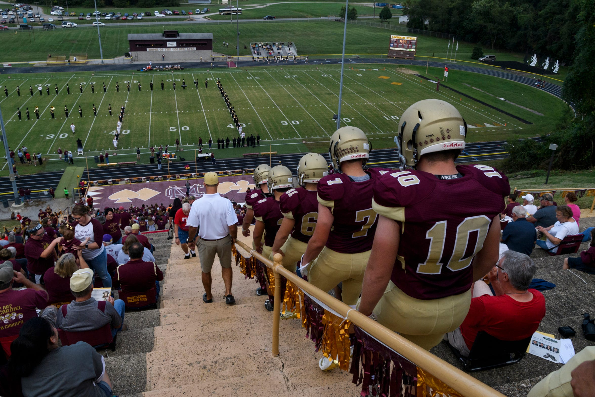 The Mount Carmel Golden Aces descend down the stairs of Riverview Stadium, known as the Snake Pit, before taking on the Washington Hatchets during Homecoming at Riverview Stadium, known as the Snake Pit, in Mount Carmel, Ill., Friday, Sept. 21, 2018. The Golden Aces defeated the Hatchets 61-20.