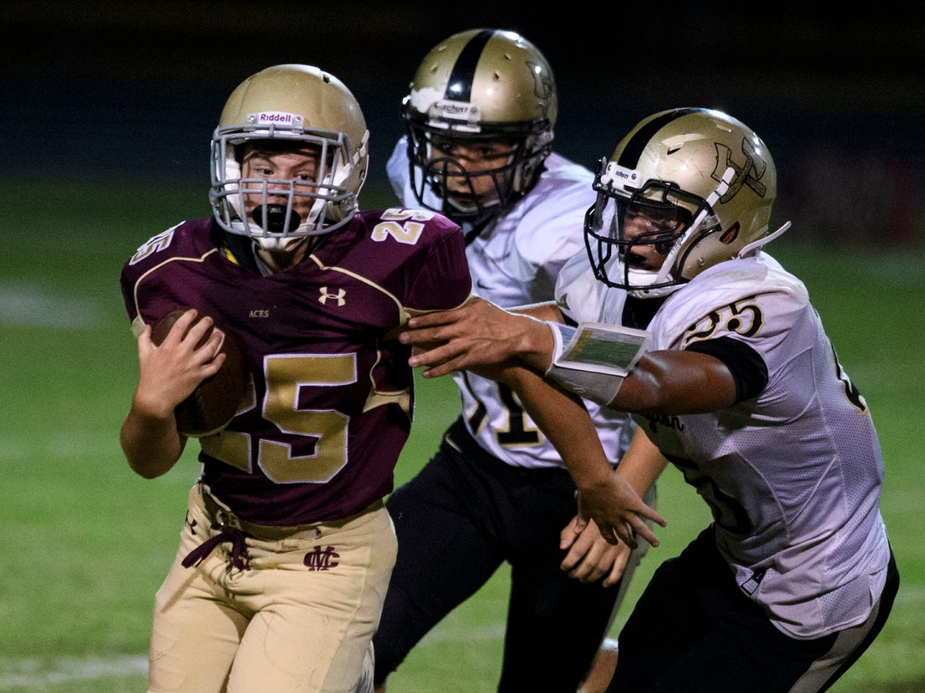 Mount Carmel's Dirk Kight (25) runs past Washington defensemen Will Lamb (51) and Julius Hardiman (25) during a Homecoming game at Riverview Stadium, known as the Snake Pit, in Mount Carmel, Ill., Friday, Sept. 21, 2018. The Golden Aces defeated the Hatchets 61-20.