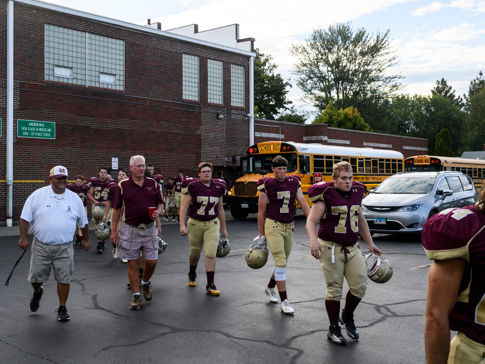 After bussing up to the top of the hill, the Mount Carmel Golden Aces walk into the locker room to prepare for their Homecoming game against the Washington Hatchets at Riverview Stadium, known as the Snake Pit, in Mount Carmel, Ill., Friday, Sept. 21, 2018. The Golden Aces defeated the Hatchets 61-20.