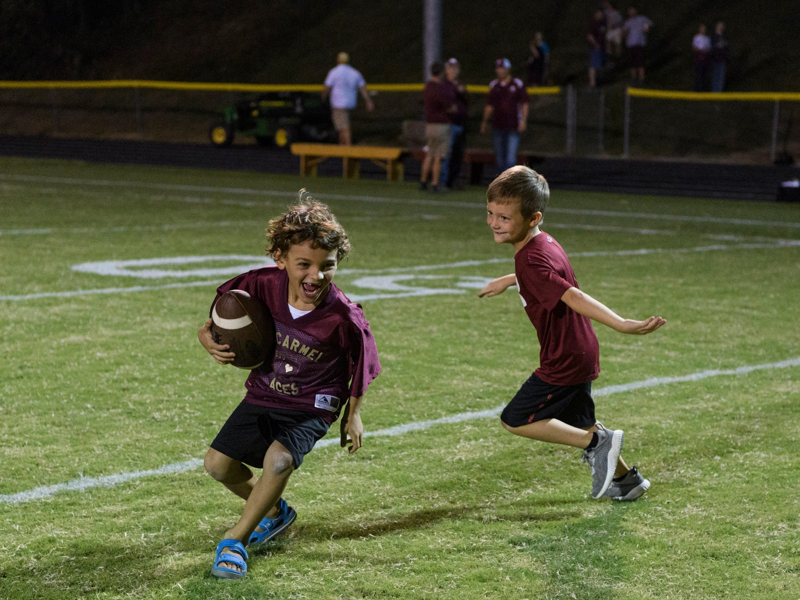 "James Brewer and Judah Brewer, two of Head Coach Michael Brewer's sons, play together on the ""Snake Pit"" field after the Mount Carmel Golden Aces defeated the Washington Hatchets 61-20 in Mount Carmel, Ill., Friday, Sept. 21, 2018."