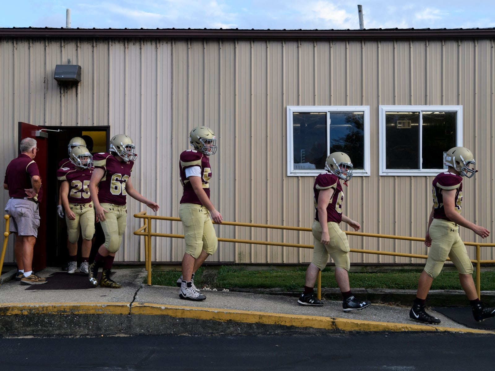 The Mount Carmel Golden Aces prepare for their descent down the stairs of Riverview Stadium, known as the Snake Pit, in Mount Carmel, Ill., Friday, Sept. 21, 2018. The Golden Aces defeated the Washington Hatchets 61-20.