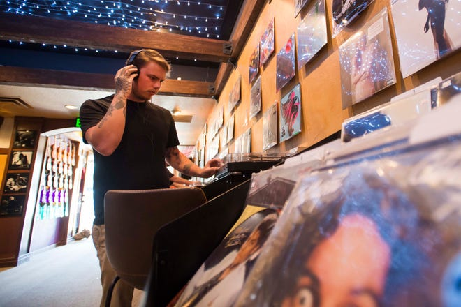"Austin Tinnel listens to a copy of Aerosmith's 1974 album ""Get Your Wings"" on Tuesday at All Sales Vinyl in Old Town Fort Collins."