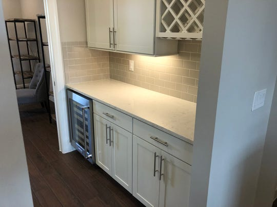 A small area off the kitchen has storage for wine, a place to serve food and storage.