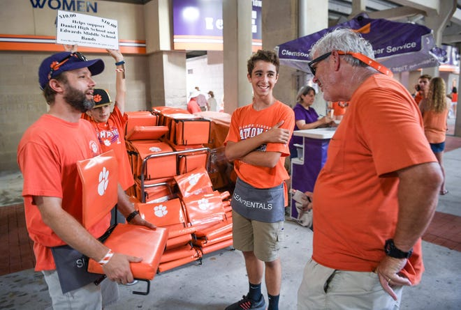 Will Chandler, left, helps football fan Don Stroup of Charlotte with a soft seat near Liam Chandler, middle, before Clemson football kickoff with Furman at Memorial Stadium in Clemson in September. The seat costs $10 to rent.