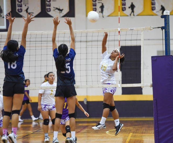 George Washington's Aubrienne Chargualaf (10) spikes over Academy players during an IIAAG High School Girls' Volleyball game at the GW High School gym on Sept. 25, 2018. Academy won in straight sets.