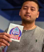 Student James Lujan, 26, displays a sticker he received after registering to vote at the Guam Community College in Mangilao in this Sept. 25 file photo.