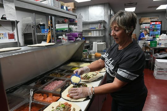 Anna Yates makes strombolis Tuesday morning as the staff at Rockhouse on the River prepare for their first day in their new riverfront location.