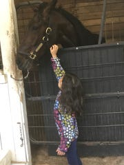 """Hickfromfrenchlick gets a little rest -- and a pat -- from Nola English. Nola's name along with her sister Maura make up the stable name Nolamaura Racing LLC, where """"Hick"""" resides."""