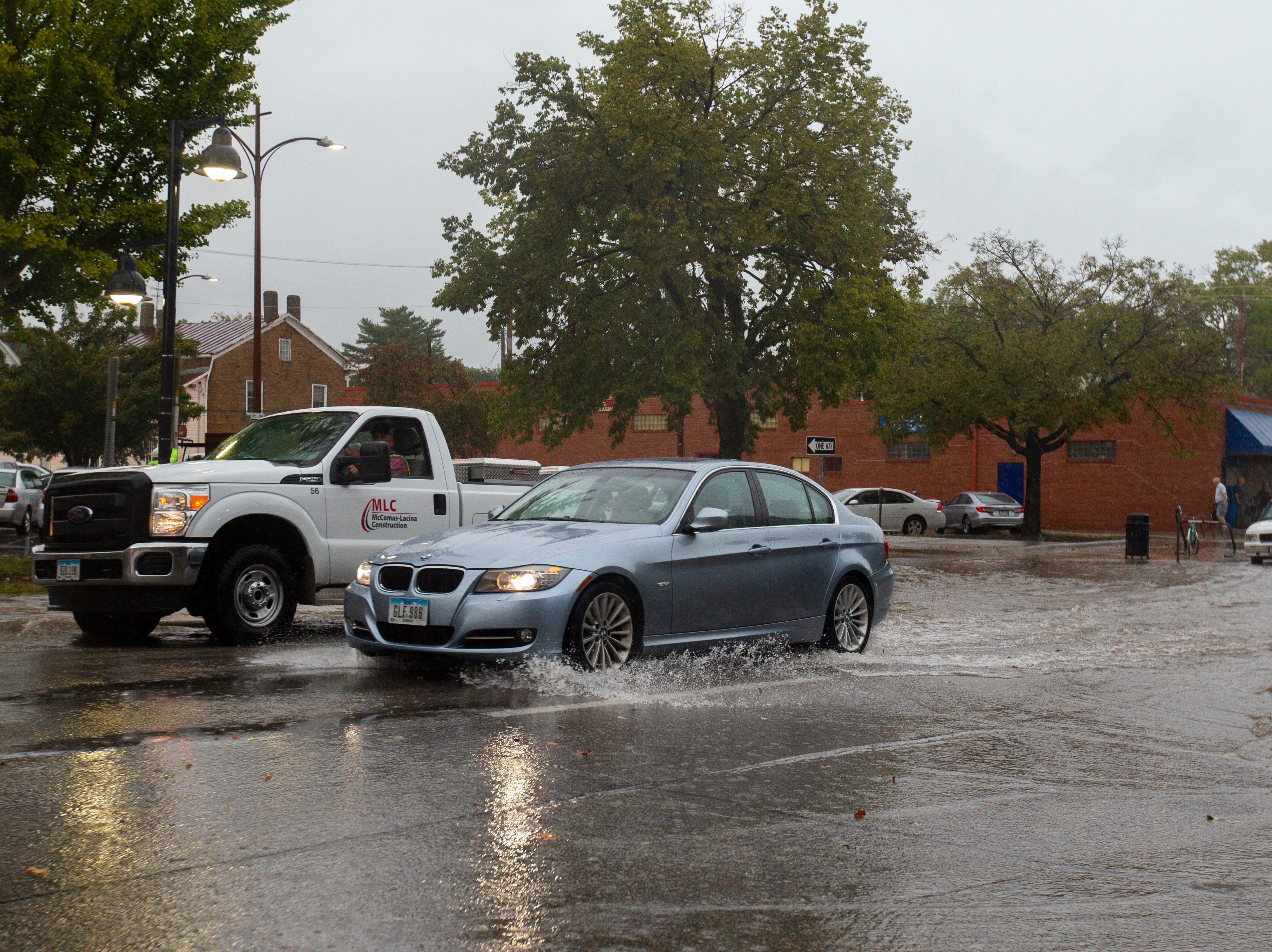 Vehicles drive through flash flooding on Tuesday, Sept. 25, 2018, along Market Street in Iowa City.