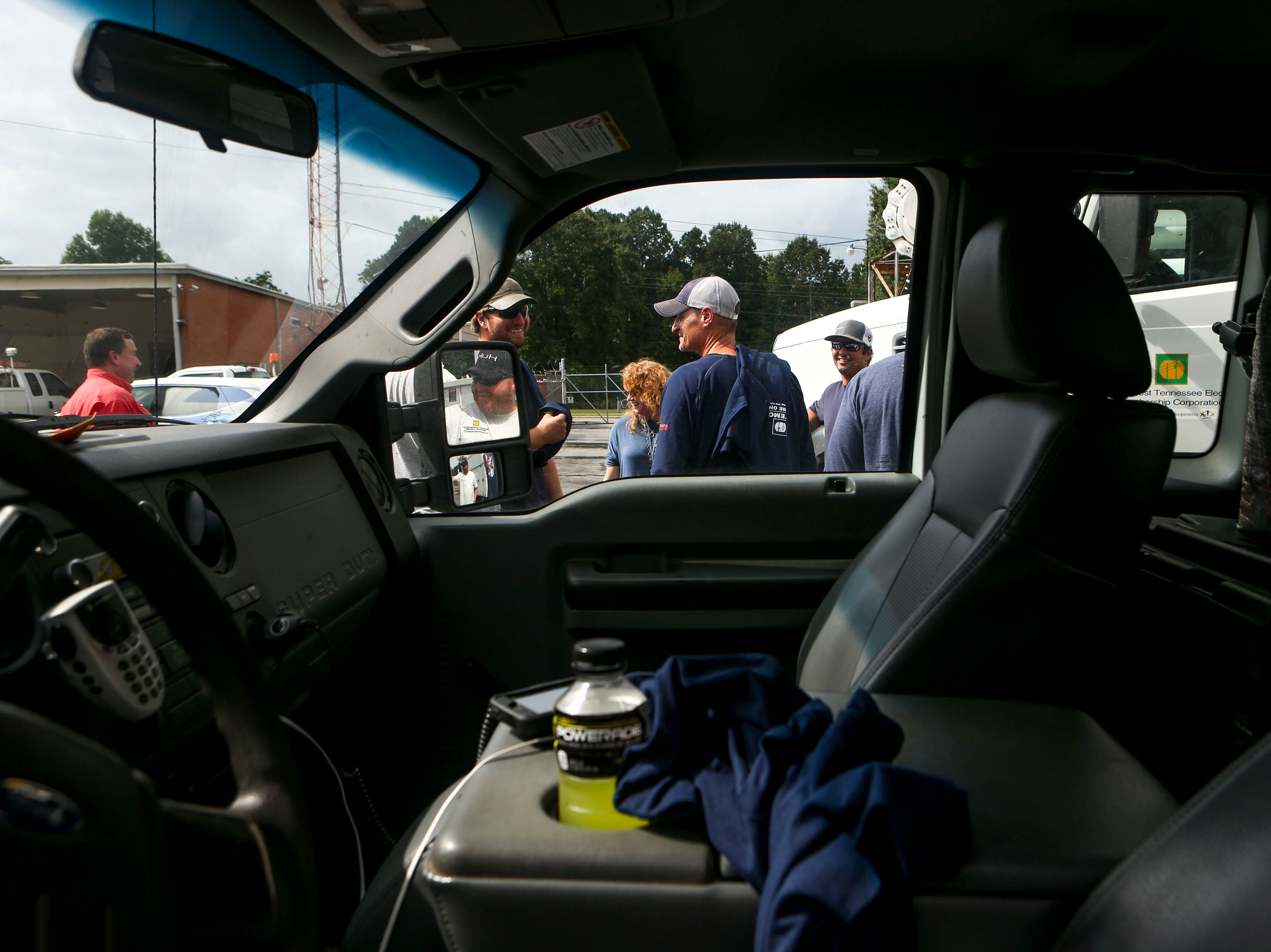 Looking through the window of a truck, linemen chat with one another and the greeting party that met to welcome them home after working in North Carolina following Hurricane Florence at Southwest Tennessee Electric in Jackson, Tenn., Monday, Sept. 24, 2018.