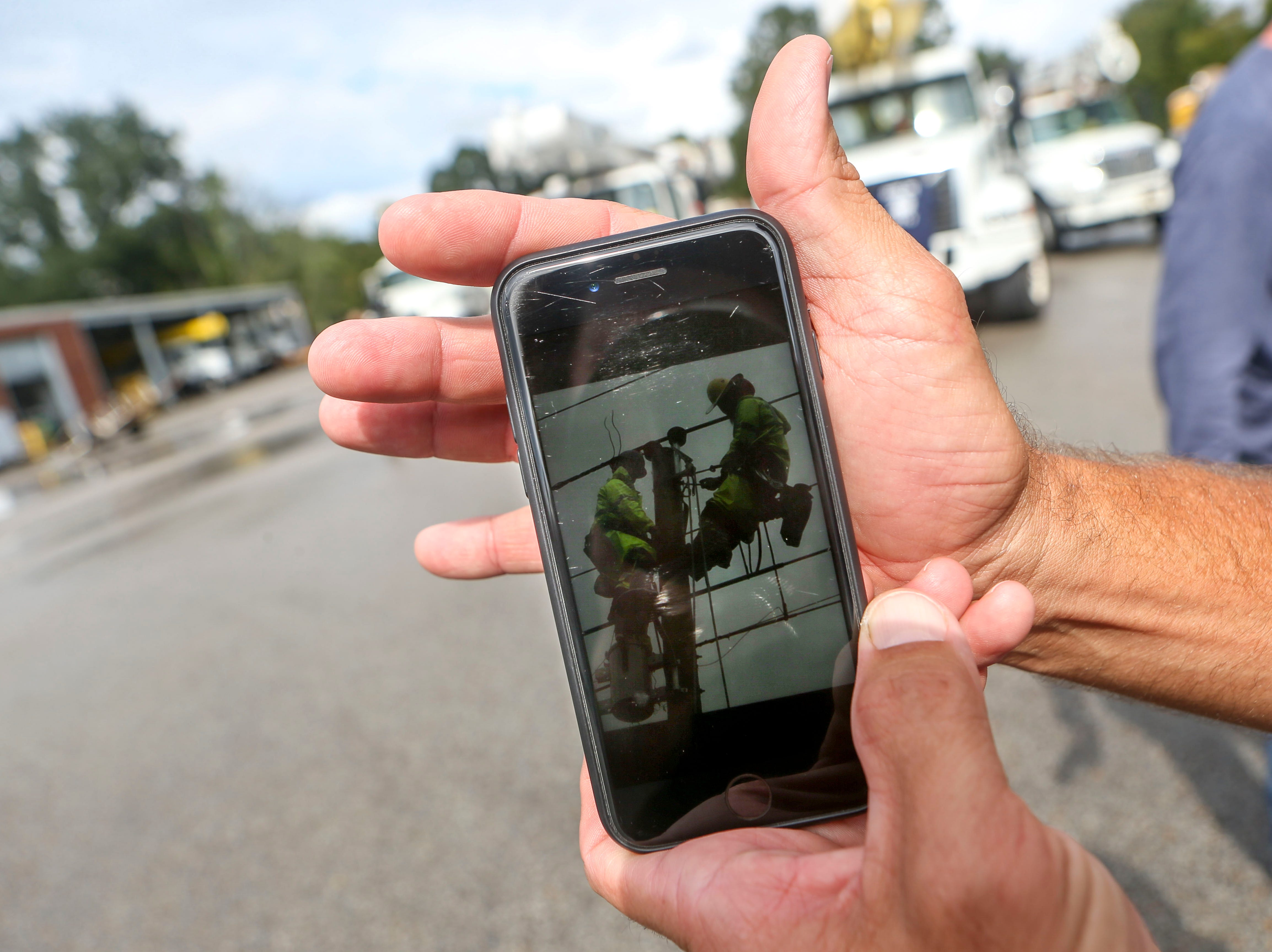 A linemen holds up his cellphone to show a photo he took of team members working in North Carolina as a part of Hurricane Florence recovery at Southwest Tennessee Electric in Jackson, Tenn., Monday, Sept. 24, 2018.