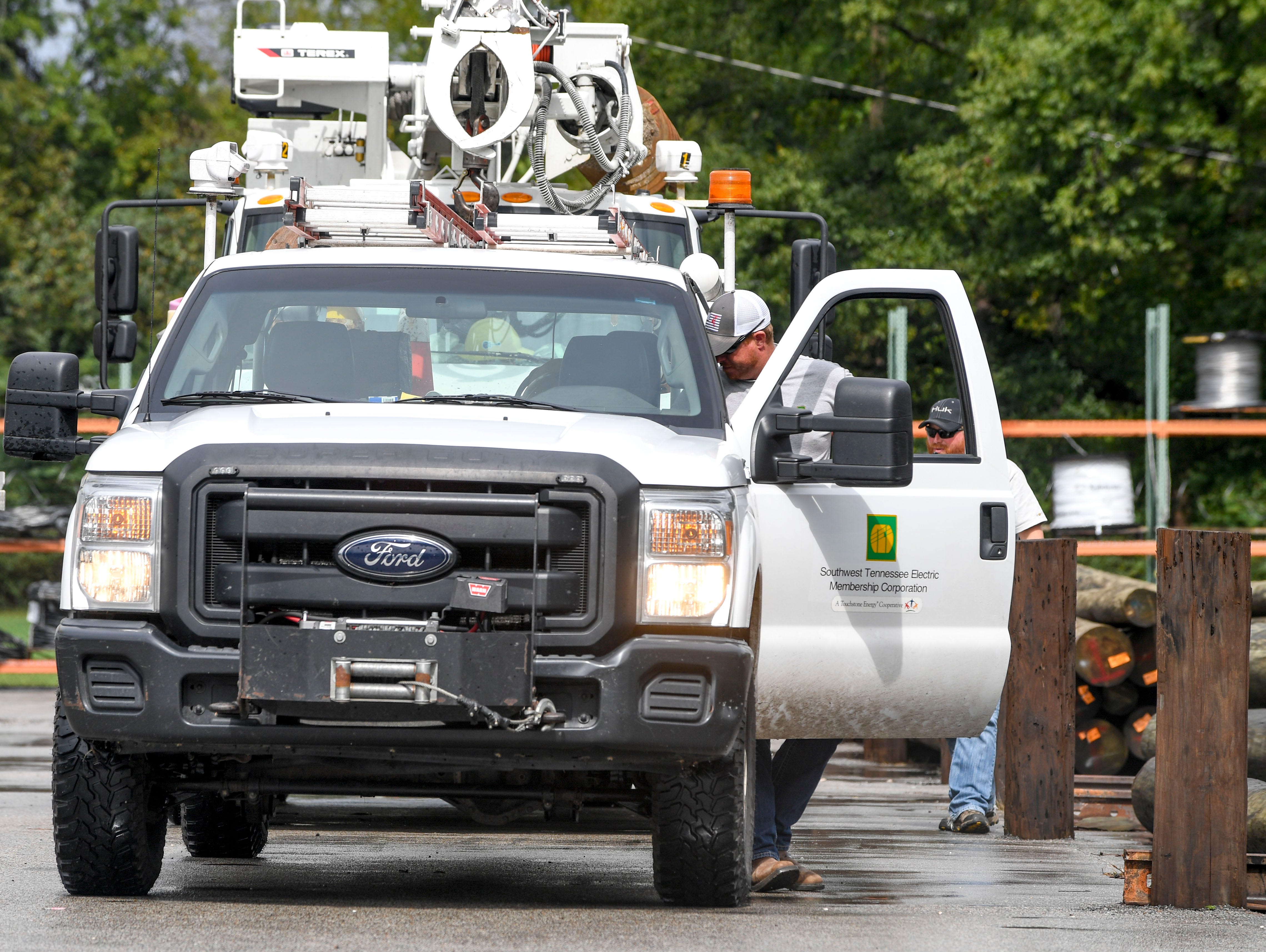 Linemen from Southwest Tennessee Electric arrive and step out of their work trucks after working in North Carolina for a week at Southwest Tennessee Electric in Jackson, Tenn., Monday, Sept. 24, 2018.